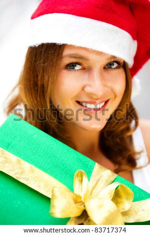 Portrait of young excited pretty woman wearing Santa Claus helper hat standing inside shopping mall smiling and holding christmas gift.