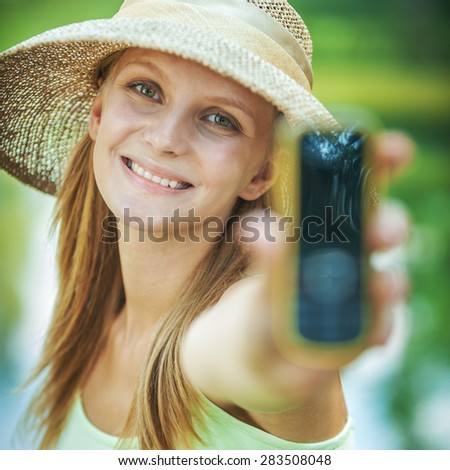 Portrait of young fair-haired woman wearing straw hat and green t-shirt, holding telephone at summer green park. - stock photo
