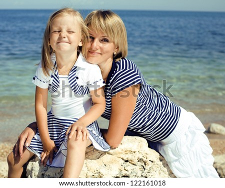 Portrait of young family having fun on the beach, mother and daughter at sea