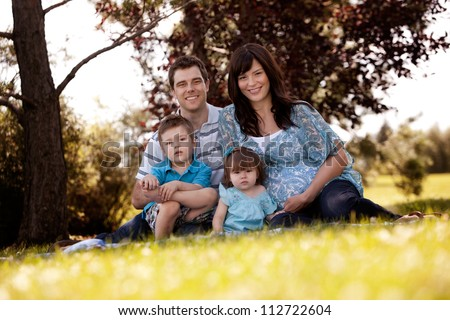 Portrait of young family in park with pregnant mother - stock photo