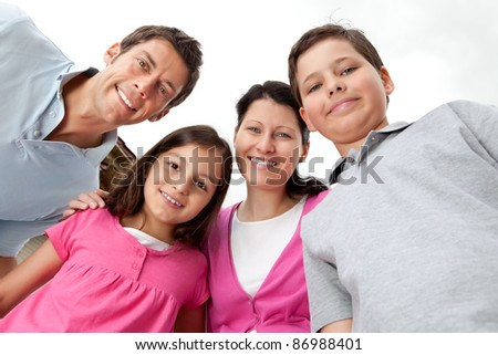 Portrait of young family looking happy against sky