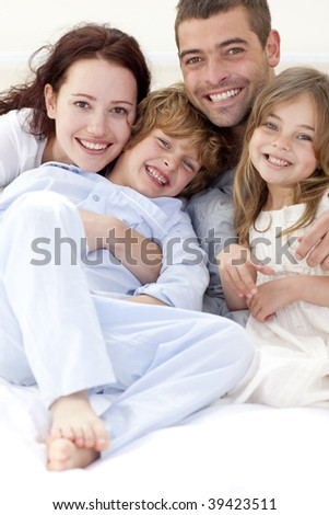 Portrait of young family lying together in bed