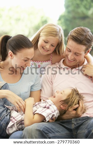 Portrait Of Young Family Relaxing On Sofa - stock photo