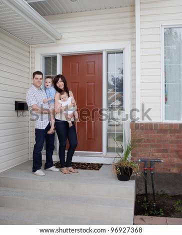 Portrait of young family standing in front of house - stock photo