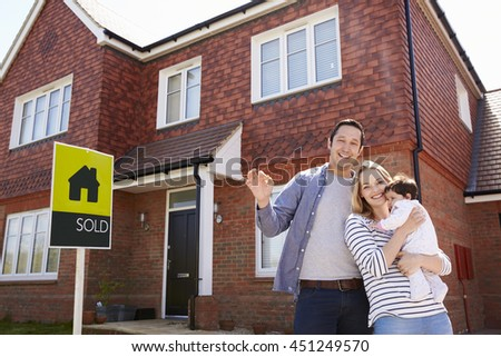 Portrait Of Young Family With Keys To New Home - stock photo