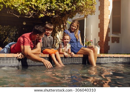 Portrait of young family with two children relaxing by their swimming pool having fun. Parents with kids sitting on the edge of pool on a sunny day. - stock photo