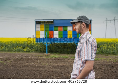 Portrait of young farmer in front of bee house