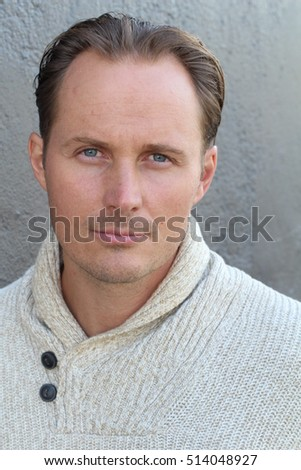 Portrait of young fashionable male model in trendy beige sweater posing over gray background. Close up. Studio shot