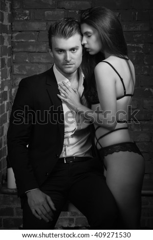 Portrait of young fashionable man and beauty brunette girl against brick wall
