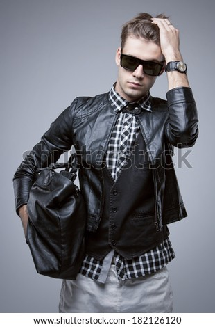 Portrait of young fashionable man in trend clothes and accessories. Isolated on grey gradient background.  - stock photo