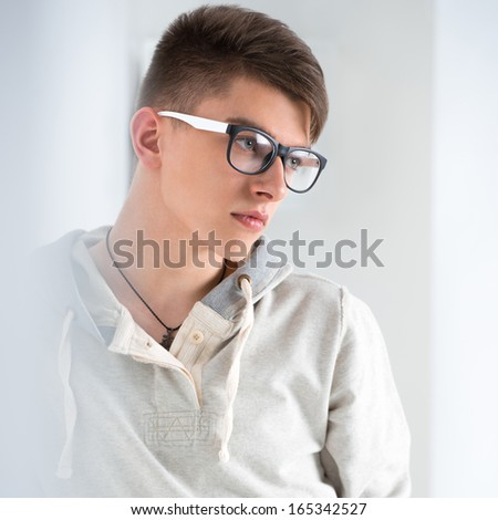 Portrait of young fashionable man leaning on white wall and wearing glasses. He is trendy fashionable