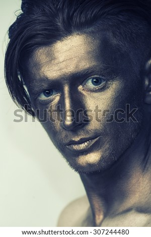 Portrait of young fashionable painted boy model with bronze bodyart on face and stylish hairdo looking forward standing in studio, vertical picture