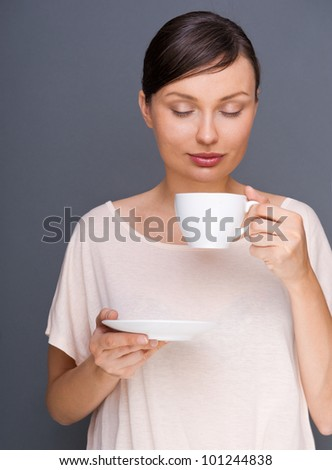 Portrait of young fashionable woman giving hot coffee or tea beverage