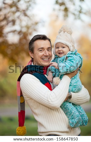 Portrait of young father and his little son in autumn park  - stock photo