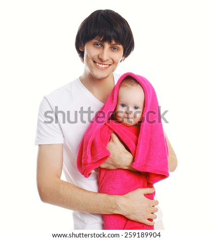 Portrait of young father holding on hands wet baby in towel - stock photo