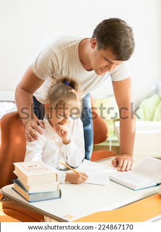 Portrait of young father looking at daughter doing homework - stock photo