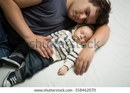 Portrait of young father sleeping on bed with newborn baby boy - stock photo