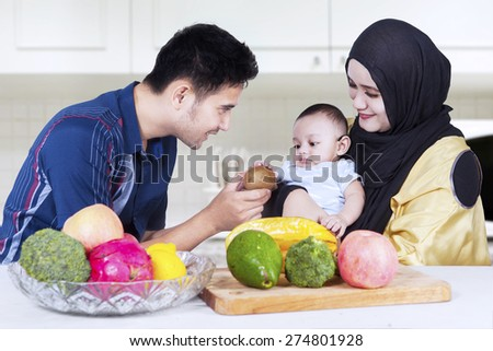 Portrait of young father with his wife give fresh fruit to his child in the kitchen