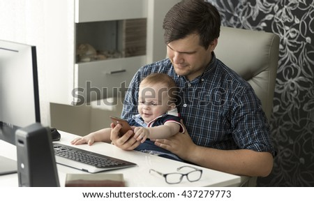 Portrait of young father working at computer playing with his baby son