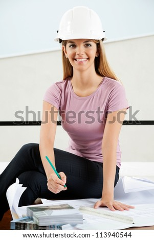Portrait of young female architect working on a blueprint