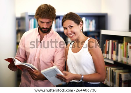 Portrait of young female asian standing with her university classmate near bookshelves in library,couple of international students holding books while looking for information while preparing for exams - stock photo