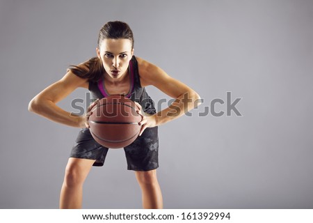 Portrait of young female basketball player passing the ball. Beautiful caucasian woman in sportswear playing basketball on grey background with copyspace - stock photo