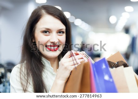 Portrait of young female buyer with shopping bags