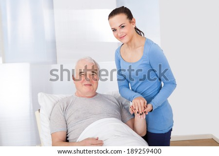 Portrait of young female caregiver comforting senior man at nursing home - stock photo