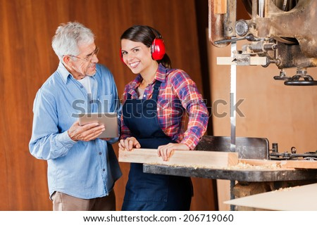 Portrait of young female carpenter with senior colleague using digital tablet in workshop - stock photo