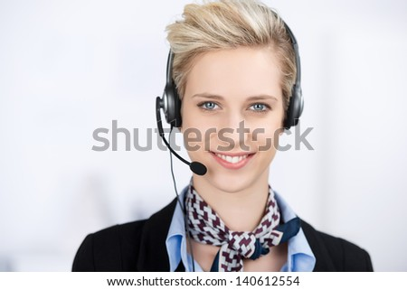 Portrait of young female customer service executive wearing headset while smiling in office - stock photo