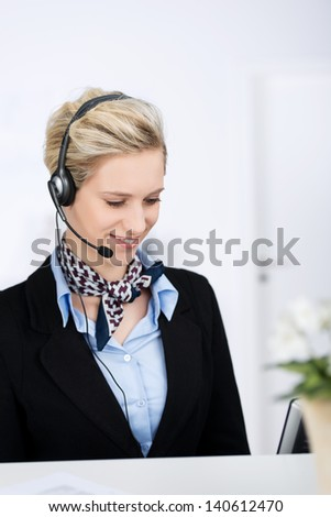 Portrait of young female customer service executive with headset while smiling in office - stock photo