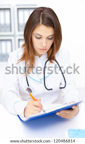 Portrait of young female doctor doing some paperwork in hospital - stock photo