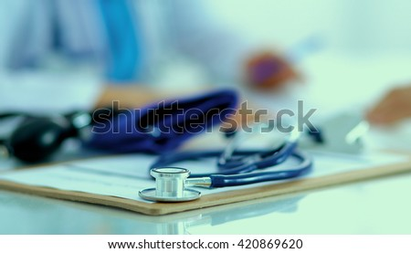 Portrait of young female doctor sitting at desk in hospital - stock photo