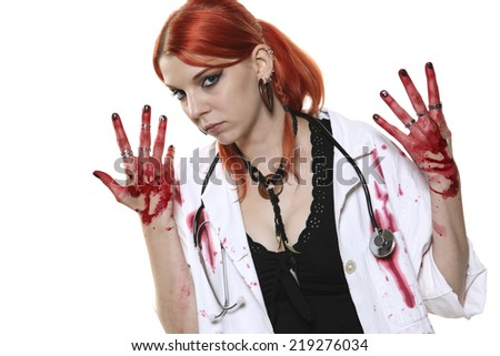 Portrait of young female doctor with blooded hands on white background - stock photo