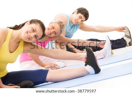 Portrait of young female doing stretching exercise among other people - stock photo