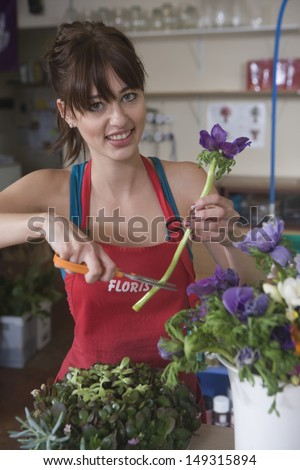 Portrait of young female florist cutting stem of flower at shop - stock photo