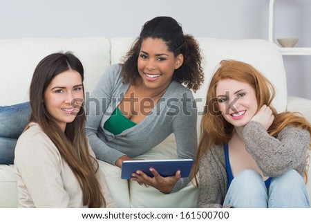 Portrait of young female friends using digital tablet together on sofa at home
