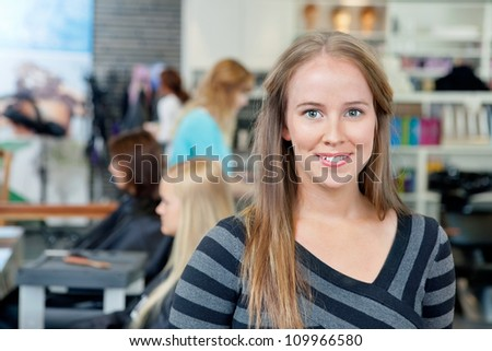 Portrait of young female hairdresser smiling with people in background