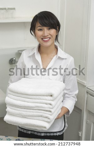 Portrait of young female housekeeper holding clean white folded towels - stock photo