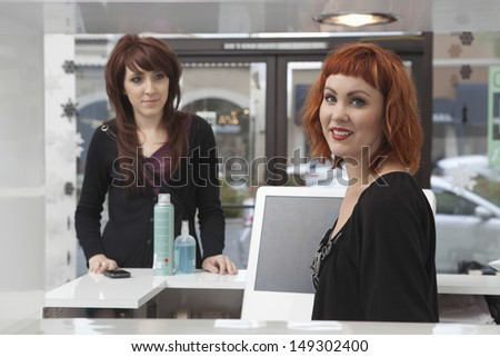 Portrait of young female owner with customer purchasing hair products in salon - stock photo