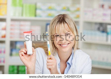 Portrait of young female pharmacist holding toothpaste and toothbrush in pharmacy - stock photo