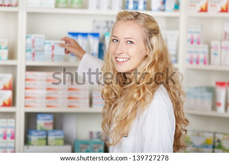 Portrait of young female pharmacist taking medicine from shelf in pharmacy - stock photo