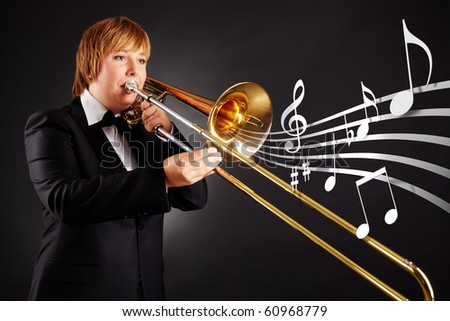 Portrait of young female playing the trombone - stock photo