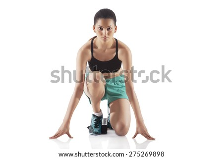 Portrait of young female runner at starting block isolated over white background - stock photo