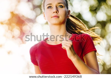Portrait of young female runner jogging in the city. - stock photo