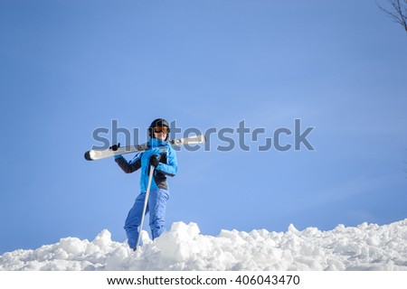 Portrait of young female skier standing on top of the mountain against blue sky on a sunny day. Woman is holding skis on her shoulder smiling and looking into the distance. Winter sports concept.