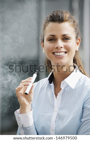 portrait of young female smoker smoking e-cigarette outdoor office building and looking at camera - stock photo