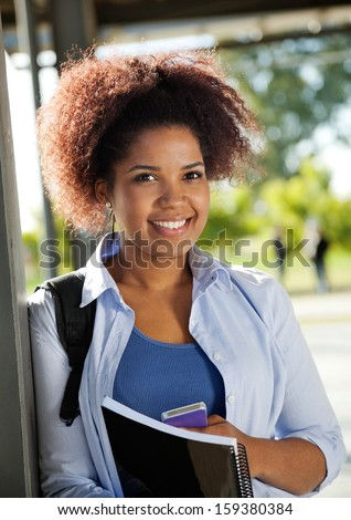 Portrait of young female student smiling on university campus