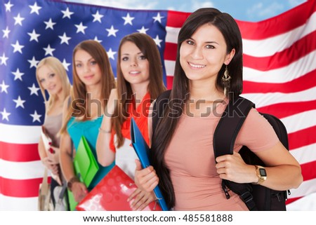 Portrait Of Young Female Students Standing In Front Of American Flag