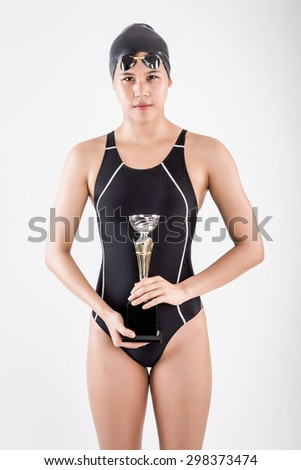 portrait of young female swimmer in blue swimsuit with goggle and swimming hat hold trophy in her hand in studio set white background - stock photo